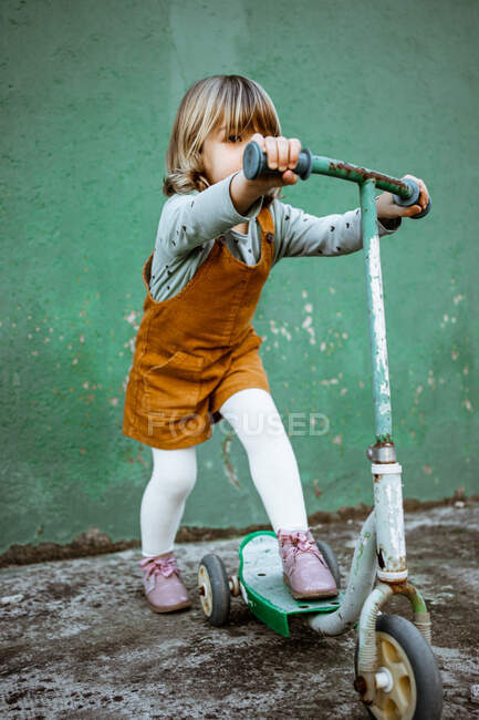 Full length little girl in casual clothes riding rusty kick scooter against shabby green wall on street — Stock Photo