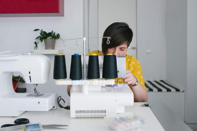 Focused brunette adult woman smiling and using sewing machine to make garment while working in home workshop — Stock Photo