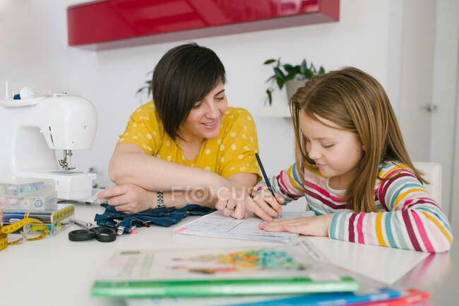 Happy adult woman smiling and helping girl with homework assignment while sewing garment at home — Stock Photo