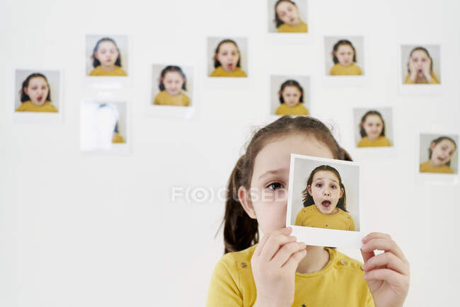 Cute little girl in yellow dress hiding face behind own picture while standing against wall with photos demonstrating various emotions — Stock Photo