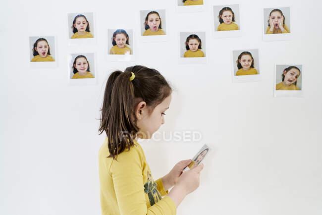 Мила дівчинка в жовтій футболці дивиться на фотографію її поруч з білою стіною з іншими фотографіями емоцій. — стокове фото