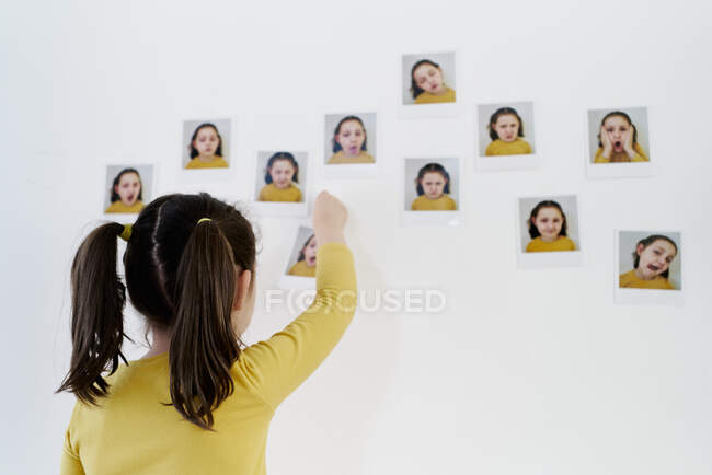 Cute little girl in a yellow dress is standing on her back placing photos of herself showing various emotions — Stock Photo