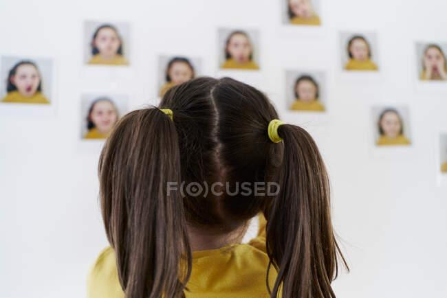 Мила дівчинка в жовтій сукні стоїть на спині і фотографує себе, показуючи різні емоції. — стокове фото