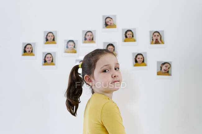 A cute little girl in a yellow dress is standing against the wall with photos showing various emotions — Stock Photo