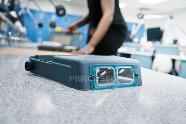 Óculos binoculares profissionais com lentes de aumento colocados na mesa de mármore perto do trabalhador em laboratório moderno — Fotografia de Stock