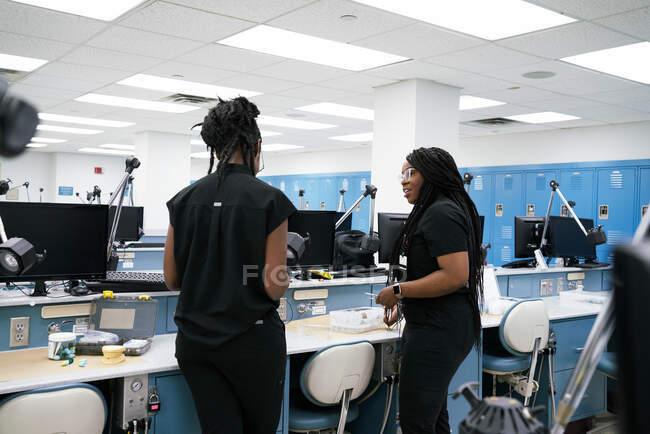 Mujeres afroamericanas con trenzas y rastas de pie cerca de la mesa y hablando entre sí mientras trabajan juntos en el laboratorio - foto de stock