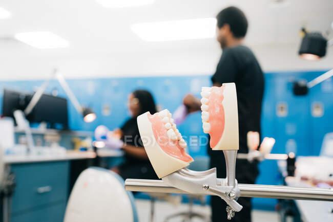 Dentes falsos ligados ao oclusivo metálico no fundo turvo do moderno laboratório ortodôntico e equipe étnica — Fotografia de Stock
