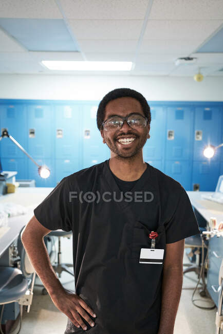 Feliz hombre afroamericano con la mano en la cintura sonriendo y mirando a la cámara durante el trabajo en el laboratorio contemporáneo - foto de stock