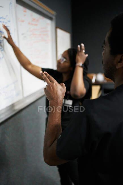 Hombre y mujer negros con trenzas leyendo y discutiendo notas en pizarra blanca mientras trabajan juntos en un laboratorio moderno - foto de stock