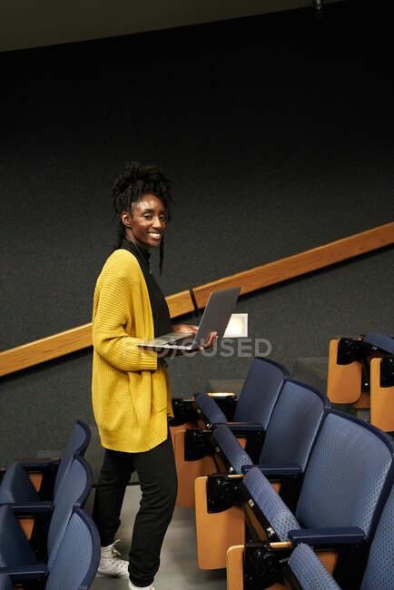 Cuerpo entero afroamericana mujer en ropa casual mirando a la cámara y el ordenador portátil de navegación, mientras que de pie en medio de filas de asientos en la sala de conferencias moderna - foto de stock