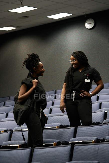 Afroamerikanische Frauen in schwarzer Uniform schauen einander an und unterhalten sich, während sie in der Nähe von Sitzreihen im Hörsaal stehen — Stockfoto