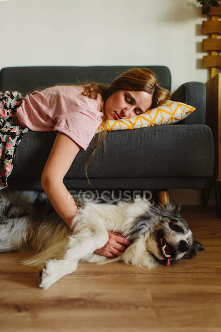 Вид сбоку взрослой женщины, трогающей смешную Колли, когда она спит на удобном диване дома — стоковое фото