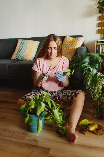 Barefoot woman with long hair sitting on floor tending potted plant with dry leaves in cozy living room at home — Stock Photo