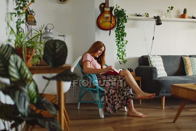 Босоногая женщина сидит на стуле, читая книгу в уютной гостиной дома — стоковое фото