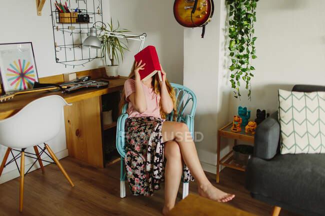 Anonyme barfüßige Frau sitzt auf Stuhl und versteckt Gesicht hinter Buch, während sie im gemütlichen Wohnzimmer zu Hause liest — Stockfoto