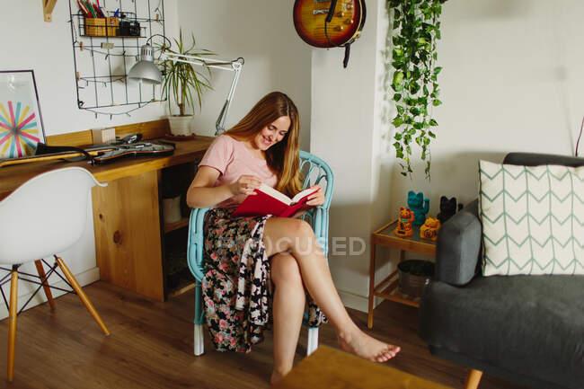 Бічний вид босоногої жінки, яка сидить на стільці, читаючи книжку в затишній вітальні вдома — стокове фото