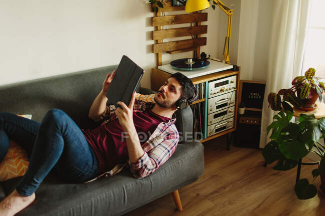 Side view of man in headphones browsing on tablet and listening to music on turntable while resting on comfortable sofa at home — Stock Photo