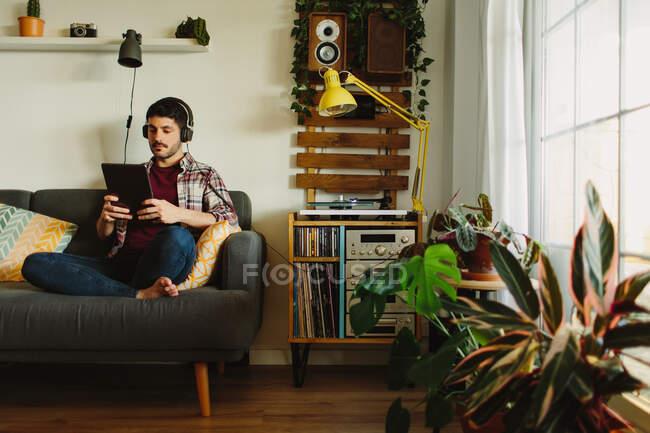 Vue latérale de l'homme dans les écouteurs naviguant sur la tablette et écoutant de la musique sur la plaque tournante tout en se reposant sur un canapé confortable à la maison — Photo de stock