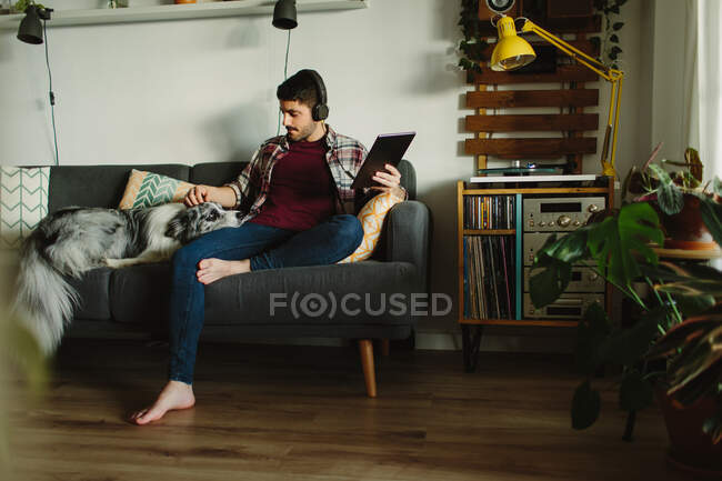 Barefooted man in headphones browsing on tablet and listening to music near turntable while resting on comfortable sofa at home with collie dog — Stock Photo