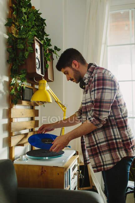 Vista laterale del giovane in abiti casual mettere disco in vinile sul giradischi prima di ascoltare musica in camera accogliente a casa — Foto stock