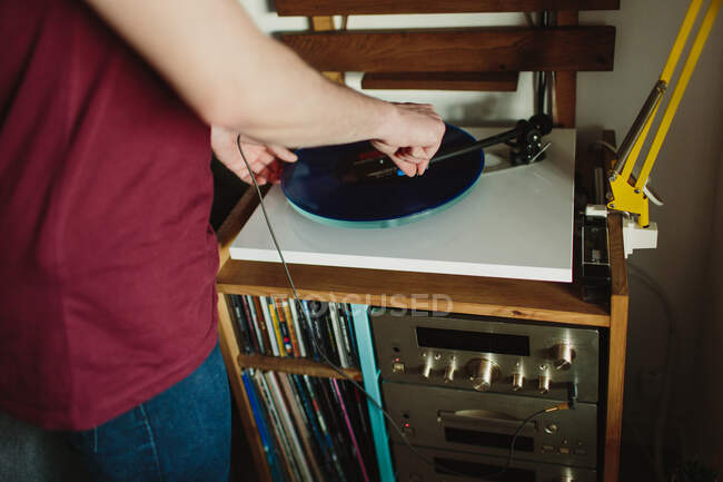 Vista laterale ritagliata di una persona irriconoscibile in abiti casual che mette un disco in vinile sul giradischi prima di ascoltare musica in una stanza accogliente a casa — Foto stock