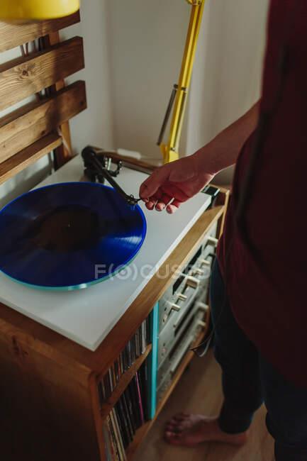 Von oben ausgeschnittene Seitenansicht einer unkenntlich gemachten Person in Freizeitkleidung, die Schallplatte auf den Plattenteller legt, bevor sie im gemütlichen Raum zu Hause Musik hört — Stockfoto