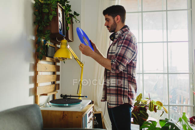 Side view of young man in casual clothes putting vinyl record on turntable before listening to music in cozy room at home — Stock Photo