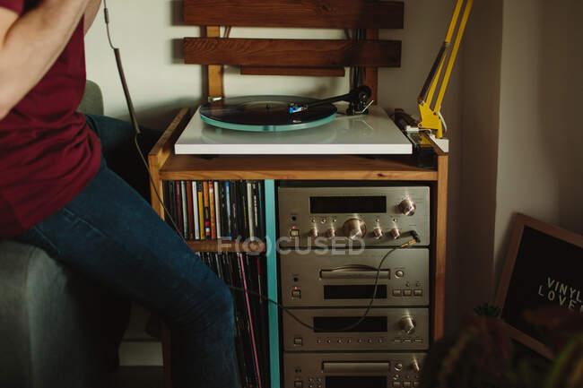 Vista lateral cortada de pessoa irreconhecível em roupas casuais colocando disco de vinil na plataforma giratória antes de ouvir música no quarto acolhedor em casa — Fotografia de Stock