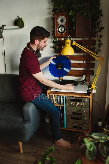 Сверху вид молодого человека в повседневной одежде, ставящего виниловую пластинку на проигрыватель перед прослушиванием музыки в уютной комнате дома — стоковое фото