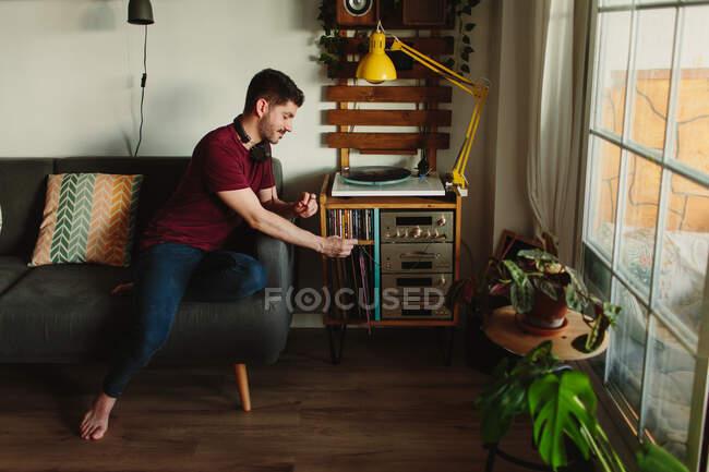 De cima vista lateral do jovem em roupas casuais colocando disco de vinil na plataforma giratória antes de ouvir música no quarto acolhedor em casa — Fotografia de Stock