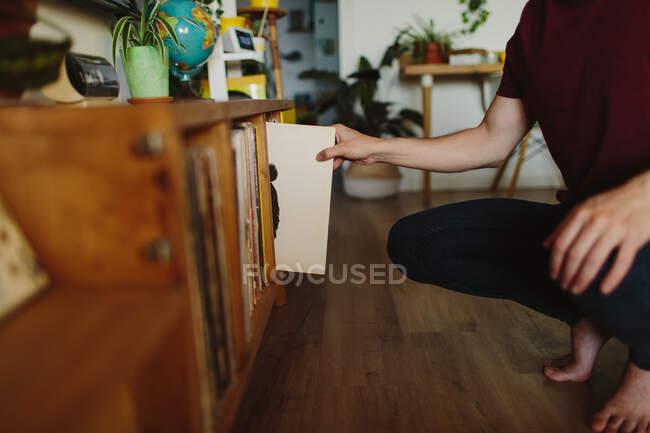 Seitenansicht des barfüßigen anonymen Mannes, der auf einer Schallplatte sitzt und im gemütlichen Raum zu Hause Vinylplatten aus dem Regal pflückt — Stockfoto