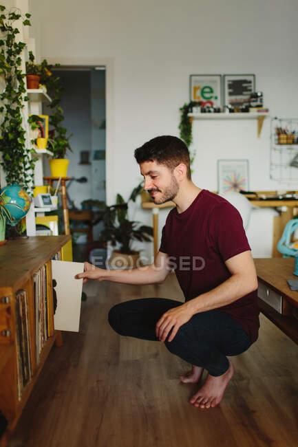 Вид сбоку на косолапого человека, сидящего на привидениях и собирающего виниловые пластинки из тряпок в уютной комнате дома — стоковое фото