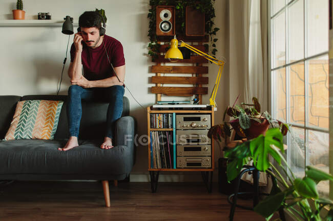 Full length barefoot guy in headphones sitting on couch and listening to music on record player in cozy living room at home — Stock Photo