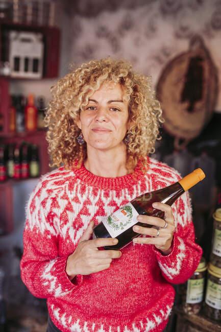 Щаслива кучерява блондинка, яка продає, тримаючи пляшку смачного вина, працюючи в місцевому продовольчому магазині. — стокове фото