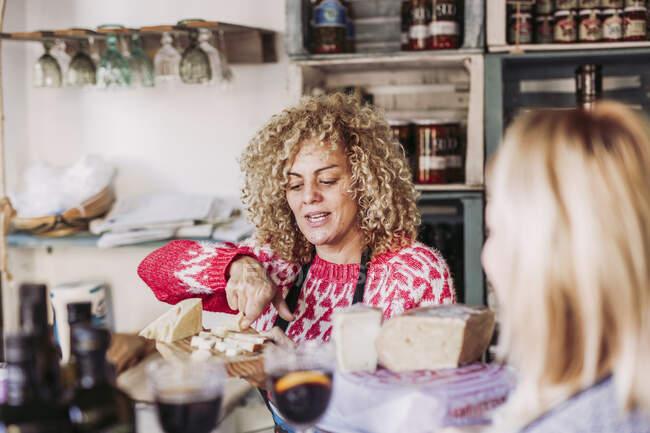 Счастливая взрослая женщина с вьющимися волосами разговаривает с клиентом во время продажи сыра в местном магазине деликатесов — стоковое фото