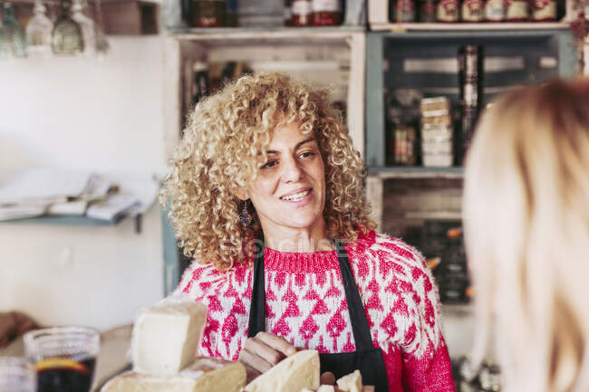 Happy adult woman with curly hair talking with customer while selling cheese in local food delicatessen store — Stock Photo