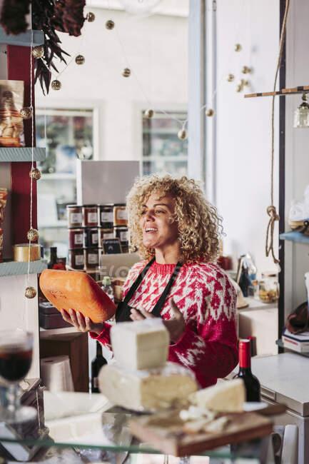 Счастливая взрослая женщина с вьющимися волосами, продающая сыр в местном магазине деликатесов — стоковое фото