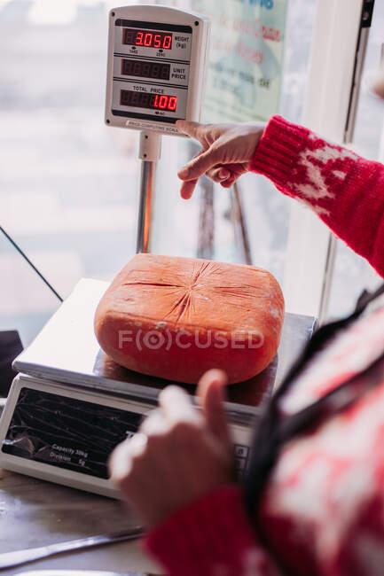 Persona irreconocible recortada que pesa queso en una máquina con pantalla electrónica colocada en el mostrador en la tienda de delicatessen de alimentos locales - foto de stock