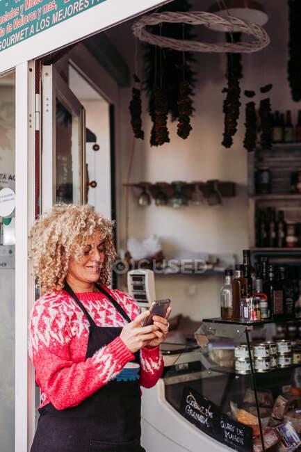 Позитивная взрослая женщина, пользующаяся мобильным телефоном, стоя у входа в местный магазин деликатесов — стоковое фото