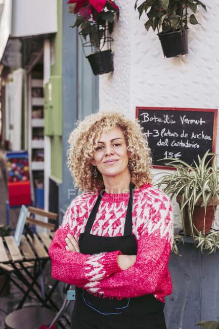 Позитивная взрослая женщина со скрещенными руками, улыбающаяся и смотрящая в камеру, стоя у входа в местный продуктовый магазин — стоковое фото