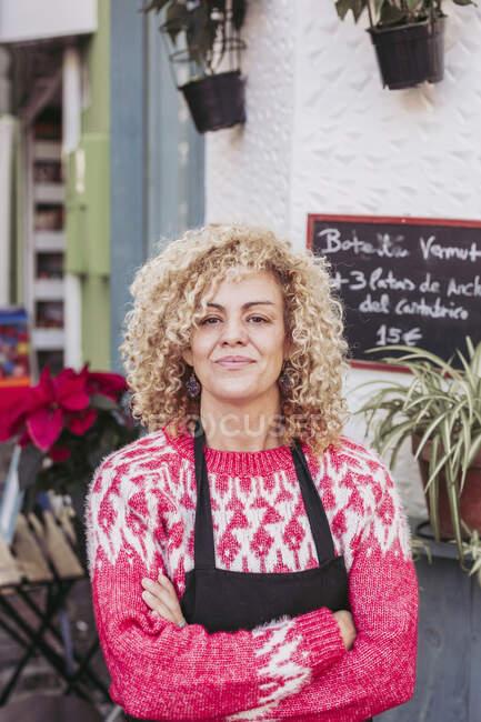 Позитивна доросла жінка зі схрещеними руками посміхається і дивиться на камеру, стоячи біля входу в місцевий продовольчий магазин. — стокове фото
