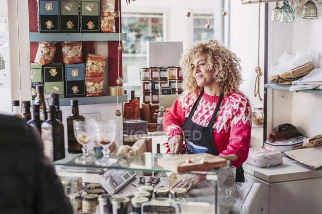 Старший чоловік вибирає їжу з морозилки, купуючи вино і сир у продавця жіночої статі в затишній маленькій крамниці. — стокове фото