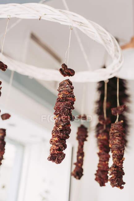 D'en bas morceaux de viande séchée délicieuse suspendus sur des cordes au plafond dans un magasin d'aliments locaux confortable — Photo de stock