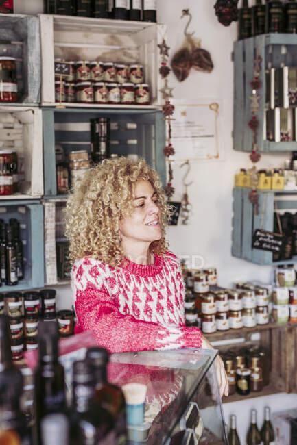 Дружелюбная взрослая женщина с вьющимися волосами, опирающаяся на полку и отворачивающаяся, работая в уютном местном магазине деликатесов — стоковое фото