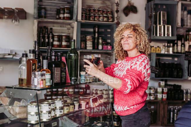 Счастливые вьющиеся волосы блондинка продавец бармен с чашкой стекла с вином во время работы в местном магазине деликатесов — стоковое фото