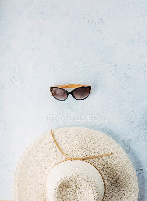 Trendy sunglasses and hat for summer vacation placed near each other on plaster surface — Stock Photo