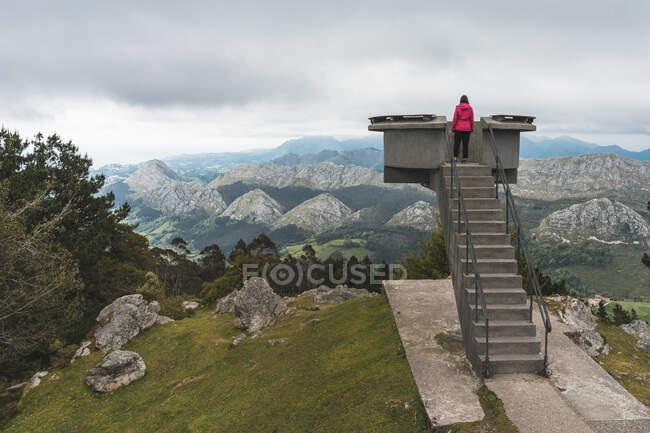 Vue arrière de la femelle anonyme en vêtements décontractés debout sur la plate-forme d'observation sur le bord de la montagne et regardant une vue fabuleuse sur les chaînes de montagnes par temps nuageux à Alicante en Espagne — Photo de stock