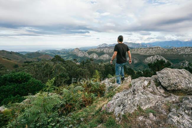 Vue arrière du mâle sans visage en tenue décontractée debout sur le bord de la falaise et profitant de paysages étonnants de chaîne de montagnes contre le ciel nuageux à Alicante en Espagne — Photo de stock