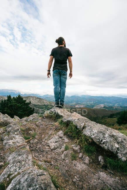 Homme méconnaissable marchant sur une colline dans la nature — Photo de stock