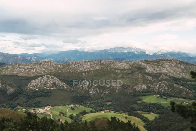 Vallée verte avec montagnes et ciel nuageux — Photo de stock